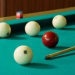 Four white billiard balls and a red ball with a cue at the green table